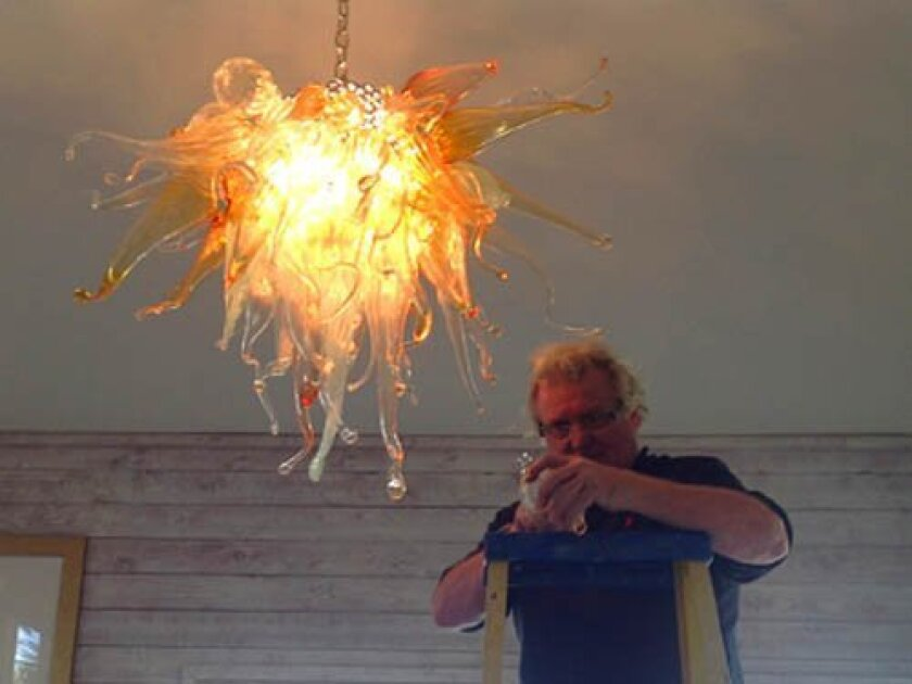 Glass artist Terje Lundaas puts finishing touches on the installation of his chandelier in the La Jolla home of Drs. Joseph and Gloria Shurman.