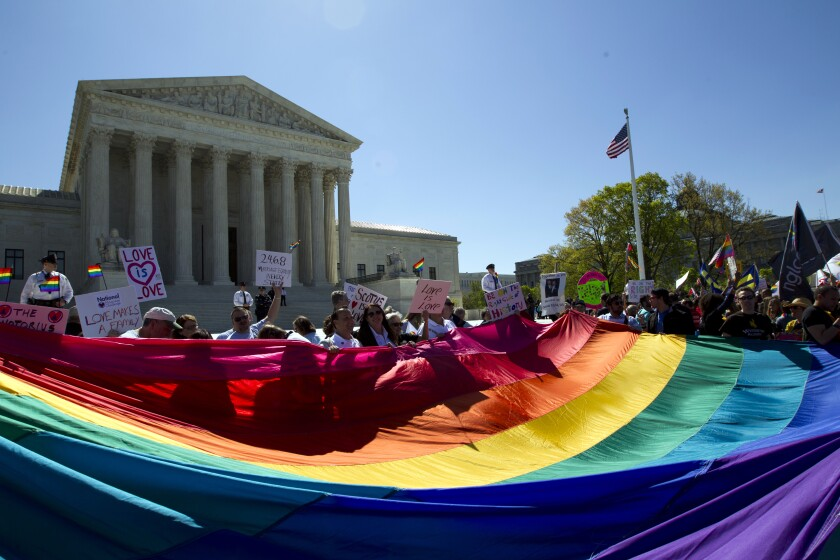 Demonstrators hold a rainbow flag outside the Supreme Court on April 28, 2015.