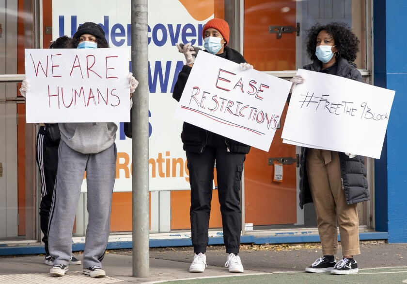 Women hold signs outside housing commission apartments under lockdown in Melbourne, Australia, on Monday, July 6, 2020. The leader of Australia's most populous state says her government's decision to close its border with hard-hit Victoria state marks a new phase in the country's coronavirus pandemic. (AP Photo/Andy Brownbill)