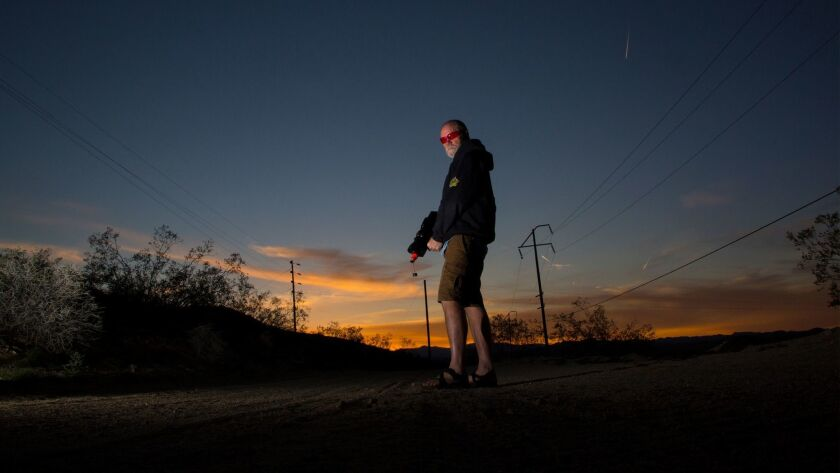 Biologist Tim Shields carries a nonlethal laser gun, which he uses to scare predatory ravens away from baby desert tortoises in Joshua Tree.