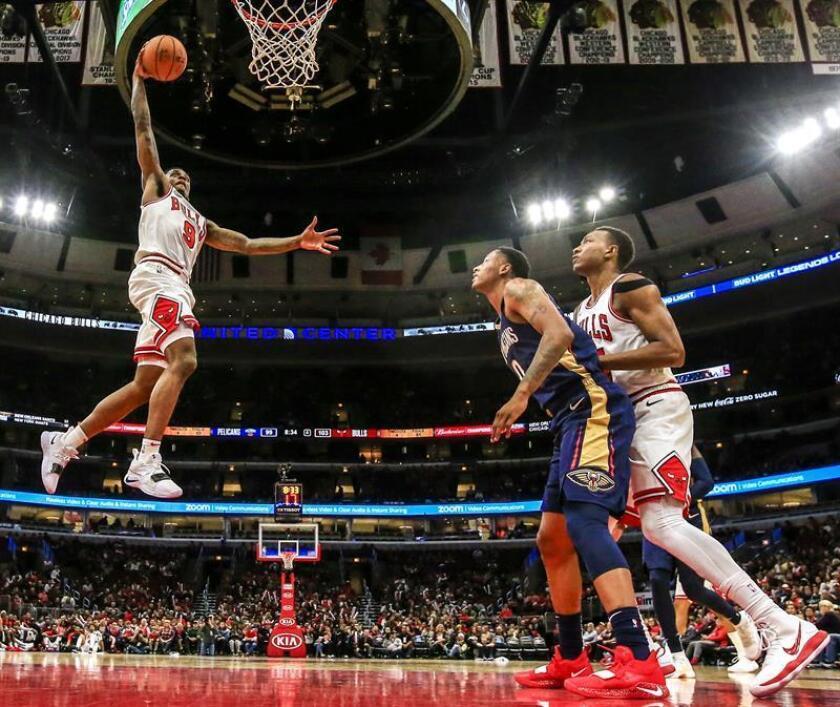 El jugador de los Chicago Bulls Antonio Blakeney (i) intenta un mate ante la defensa de Darius Morris (c), de los Pelicans de Nueva Orleans y Wendell Carter Jr. (d), de los Bulls, durante el partido celebrado en el United Center de Chicago, Illinois. EFE