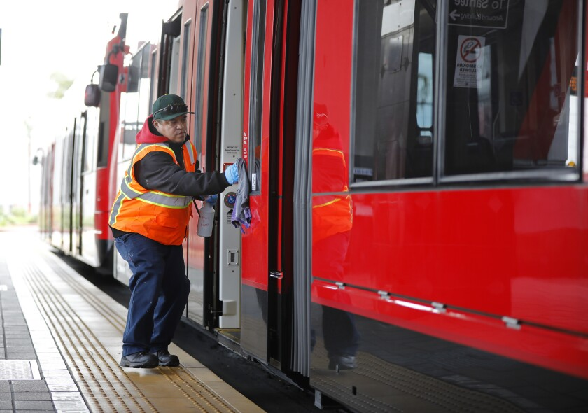 A man cleans trolley doors. San Diego's climate action plan may include strategies to get people using public transit.