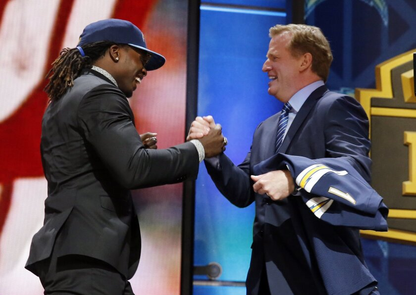 Wisconsin running back Melvin Gordon celebrates with NFL commissioner Roger Goodell after being selected by the San Diego Chargers as the 15th pick in the first round of the 2015 NFL Draft,  Thursday, April 30, 2015, in Chicago. (AP Photo/Charles Rex Arbogast)