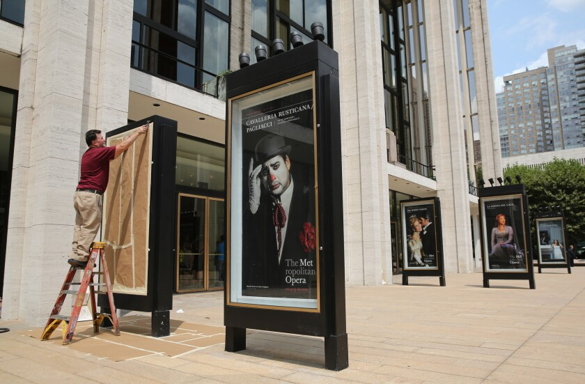 A worker unveils an advertisement for future productions at the Metropolitan Opera at Lincoln Center in New York. The ongoing labor dispute may jeopardize the upcoming Met season.