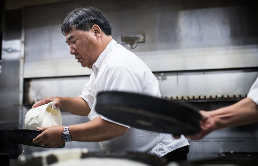 LOS ANGELES, CA - June 13, 2018 Youlen Chan pours cake batter at Phoenix Bakery in Chinatown, a fam