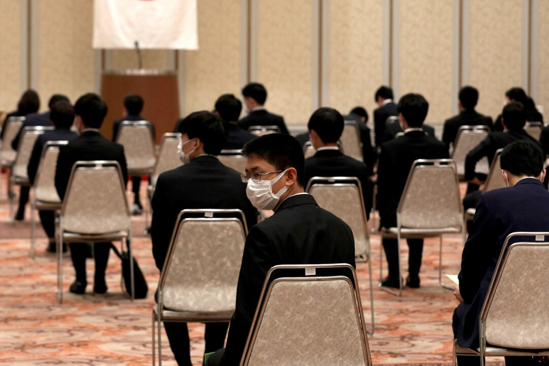 JAPAN: New employees wear face masks as they observe social distancing during an initiation ceremony at the Himeji Chamber of Commerce and Industry hall on Wednesday in Himeji, Japan.