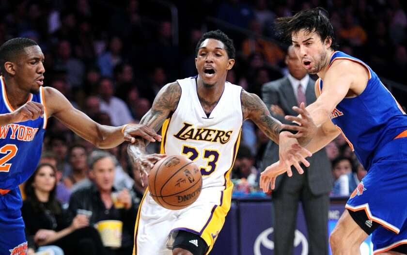 Lakers guard Lou Williams is fouled by Knicks guard Sasha Vujacic, right, as Langston Galloway tries to help on defense on March 13.