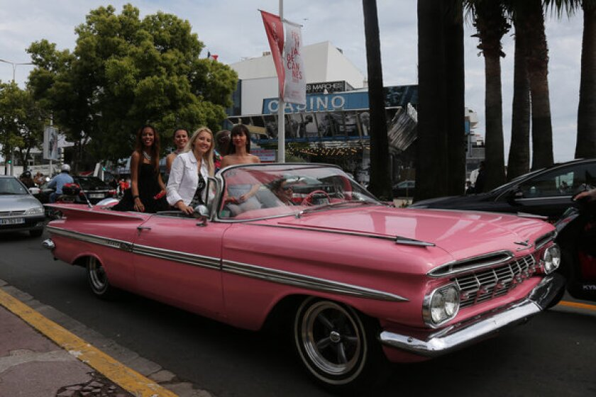 Women ride on La Croisette in a pink vintage Chevrolet Impala hours before the opening of the 66th Cannes Film Festival on Wednesday.