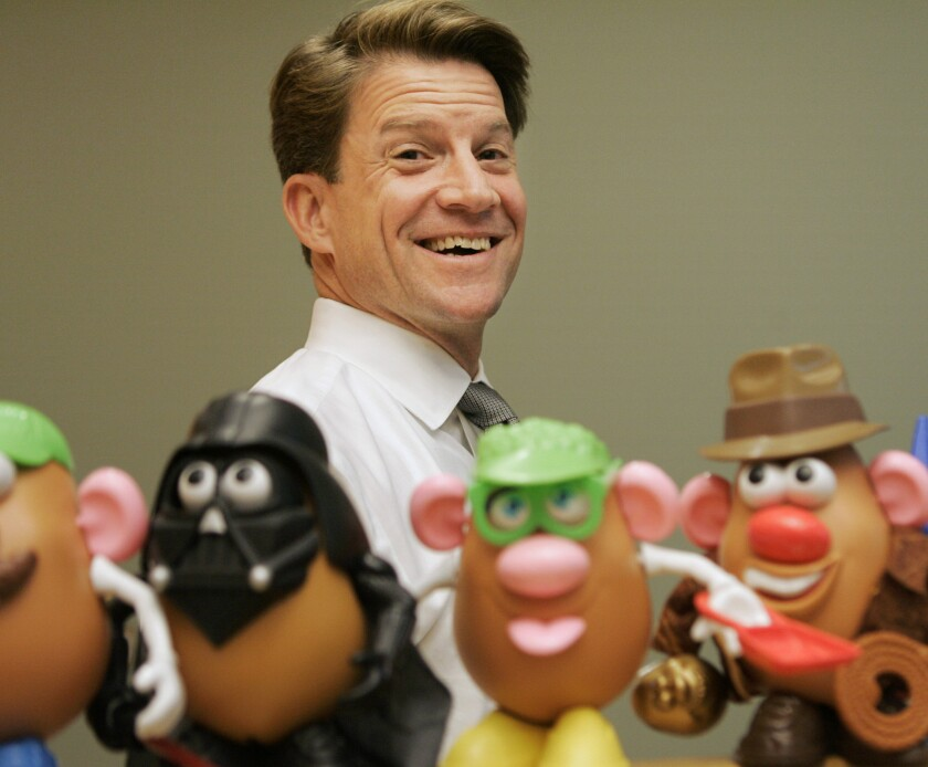 Hasbro chief Brian Goldner stands next to some of the company's toy figures.