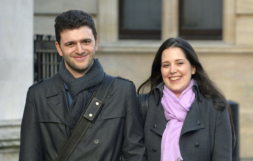 """Louisa Hodkin and her fiancee Alessandro Calcioli stand outside the Supreme Court in London, Wednesday Dec. 11, 2013, after winning their battle to marry in a Church of Scientology chapel. Louisa Hodkin had gone to the U.K. Supreme Court after a High Court judge ruled that Scientology services were not """"acts of worship."""" (AP Photo/PA, John Stillwell) UNITED KINGDOM OUT NO SALES NO ARCHIVE"""