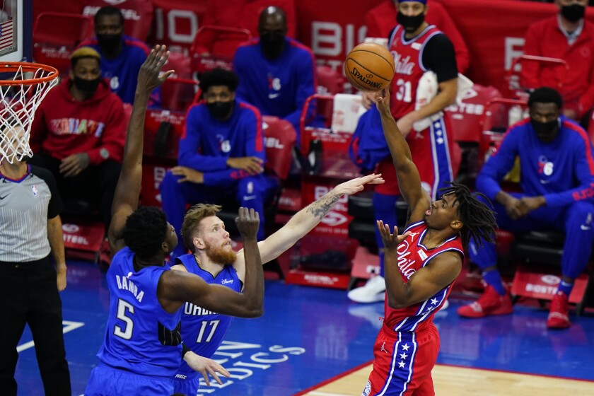 Philadelphia 76ers' Tyrese Maxey, right, goes up for a shot against Orlando Magic's Ignas Brazdeikis, center, and Mo Bamba during the second half of an NBA basketball game, Friday, May 14, 2021, in Philadelphia. (AP Photo/Matt Slocum)