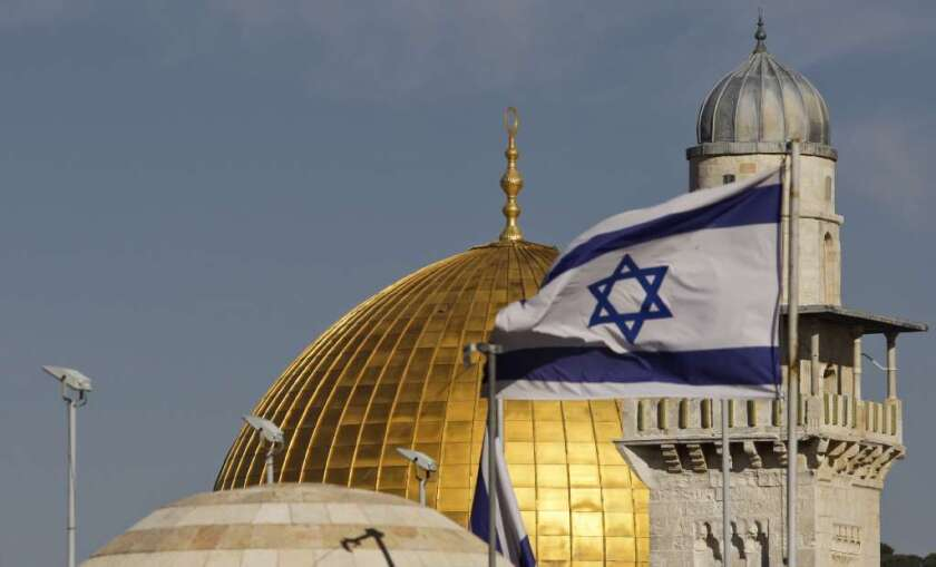 Will a two-state or one-state solution be the better option for Mideast peace? Above, an Israeli flag waves near the Dome of the Rock Mosque in Jerusalem.