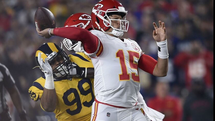 Kansas City Chiefs quarterback Patrick Mahomes (15) passes under pressure from Los Angeles Rams defe