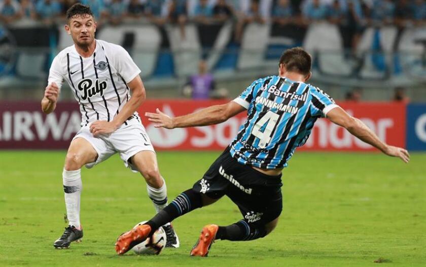 Walter Kannemann (d) de Gremio en acción contra Adrián Martínez (i) de Libertad este martes, durante un partido de Copa Libertadores entre Gremio de Brasil y el Libertad de Paraguay, en el estadio Arena do Gremio, en Porto Alegre (Brasil). EFE