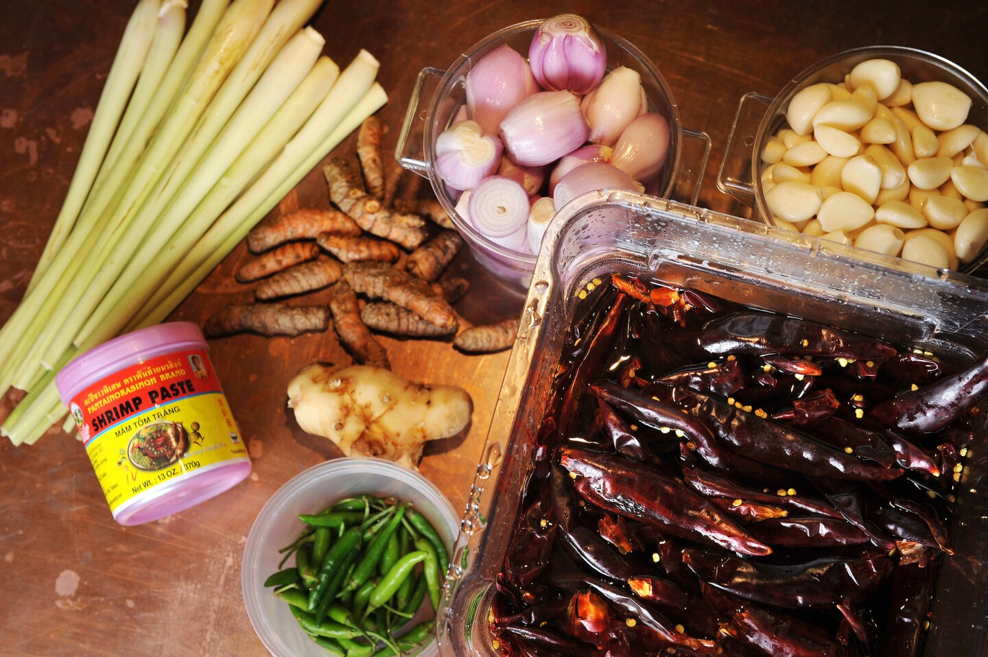 Some of the ingredients needed for the turmeric and coconut curry including (from left) lemongrass, shrimp paste, turmeric, galangal, shallots, garlic, Thai green chiles and Puya chiles.