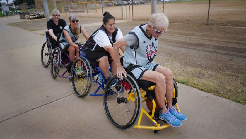 Coming in from the parking lot,74-year old Keri Gloyna leads her team to their basketball practice i