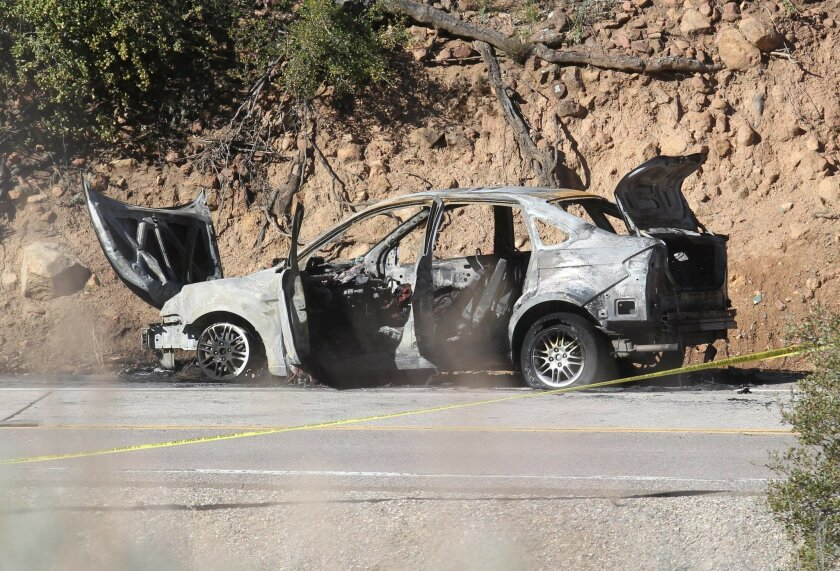 The burnt remains of a car rest in the eastbound lanes of Old Highway 80 after it burst into flames following a chase with a Border Patrol agent. The car's driver died and the agent was injured when the vehicle exploded.