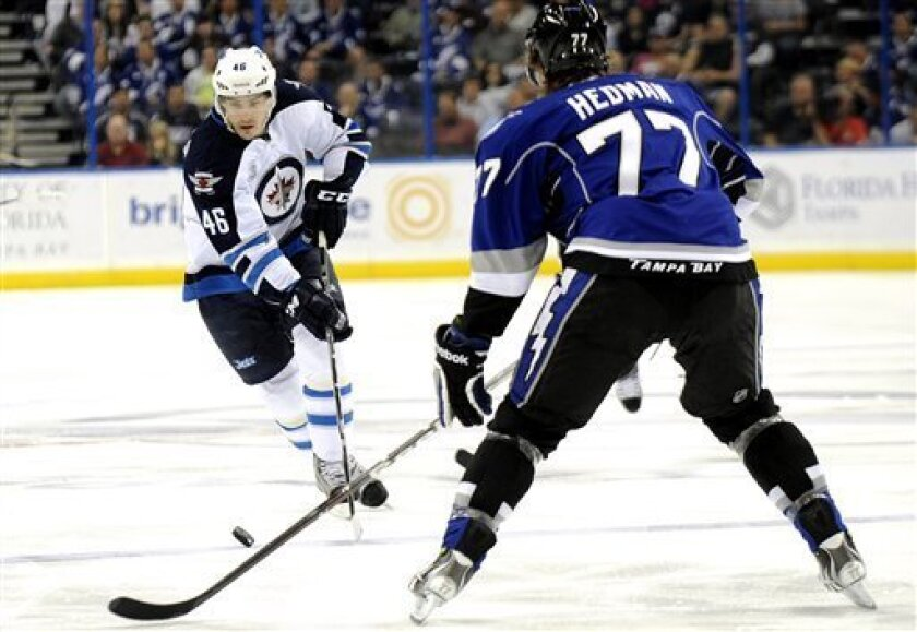 Winnipeg Jets right wing Spencer Machacek, left, controls the puck against Tampa Bay Lightning defenseman Victor Hedman, of Sweden, during the first period of an NHL hockey game on Saturday, March 31, 2012, in Tampa, Fla. (AP Photo/Brian Blanco)