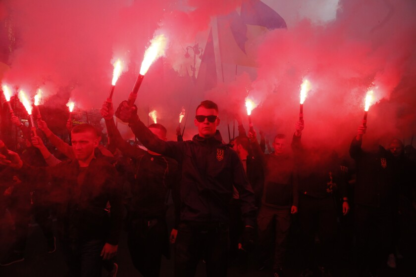 Members of the nationalist movements light flares during a rally marking Defense of the Homeland Day in Kyiv, Ukraine, on Monday.