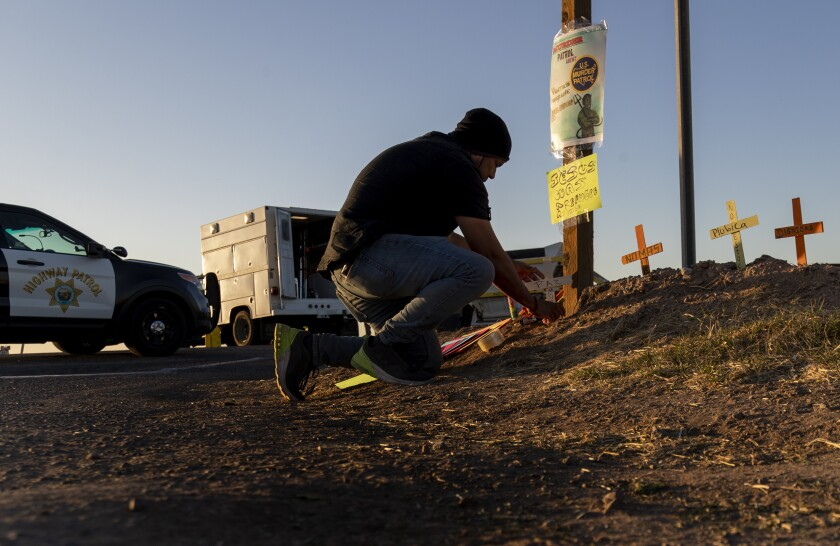 A man kneels to place small wooden crosses in the dirt