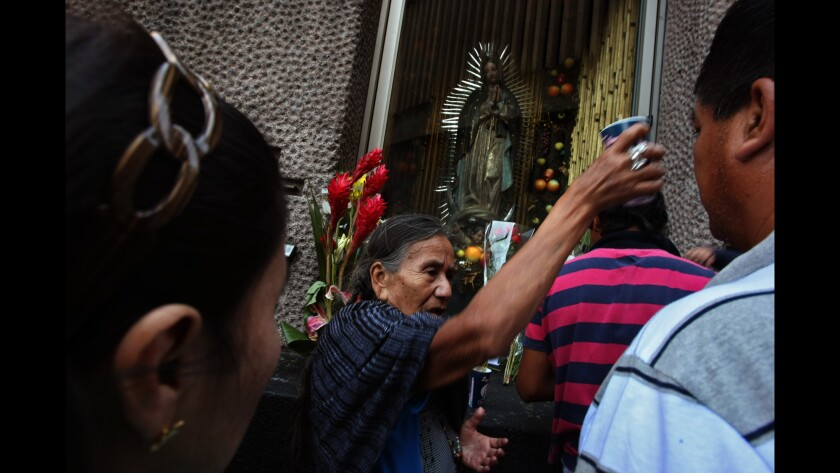A woman prays over pilgrims at the Basilica of Our Lady of Guadalupe in Mexico City in 2013. The shrine is where Pope Francis will celebrate Mass on Feb. 13, 2016.