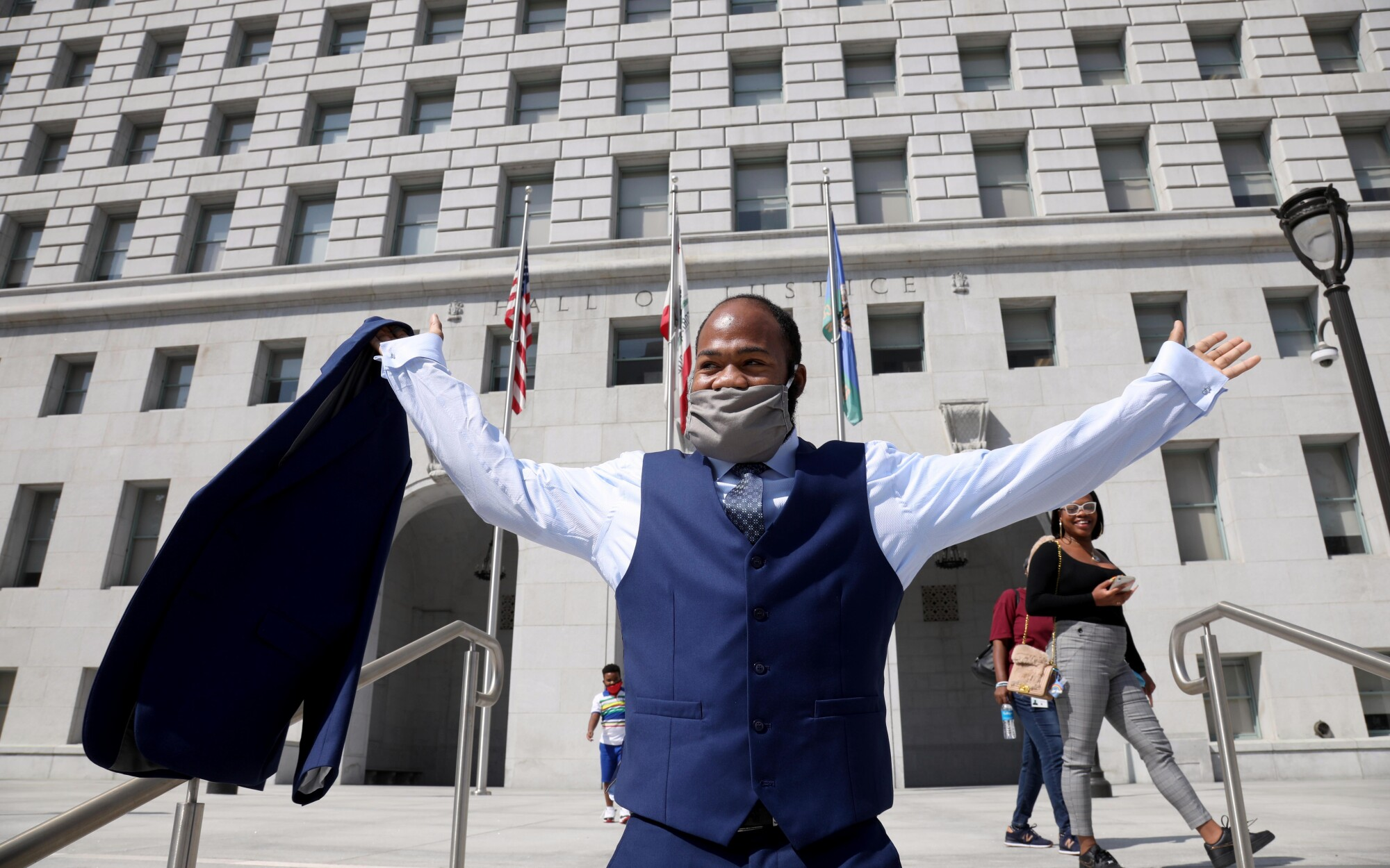 Derrick Harris raises his arms outside the Hall of Justice in Los Angeles.