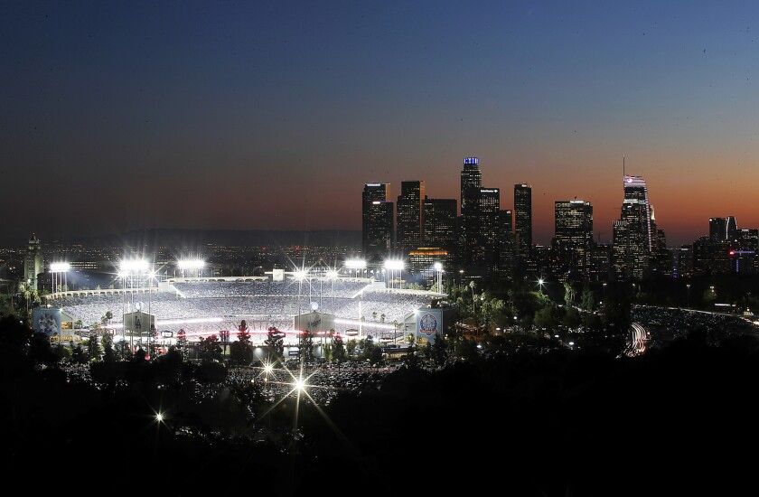 Dodger Stadium in prepandemic times, with downtown L.A. lighted in the distance.