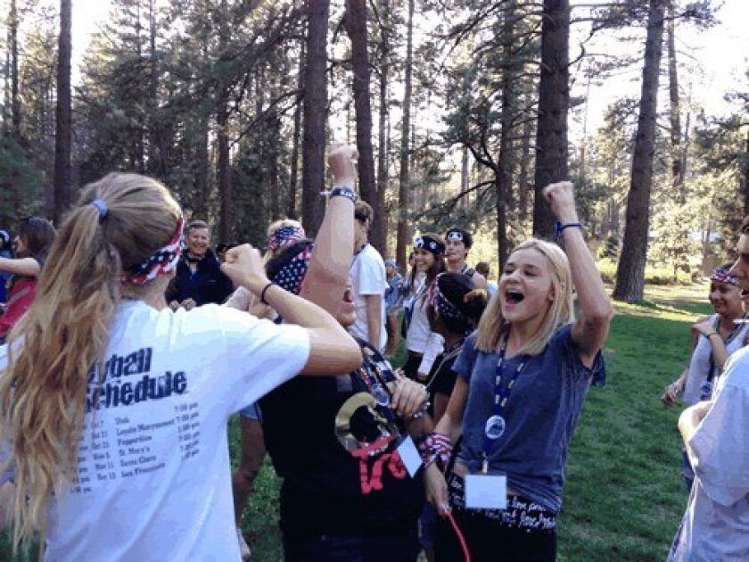 Students cheer their success in a team-building exercise.