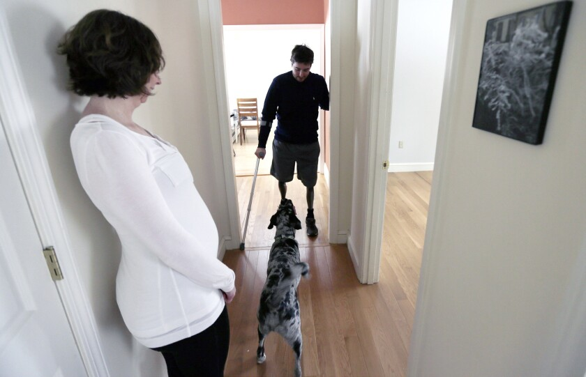 Jeff Bauman talks to his dog Bandit as his fiancee Erin Hurley watches at their home in Carlisle, Mass.