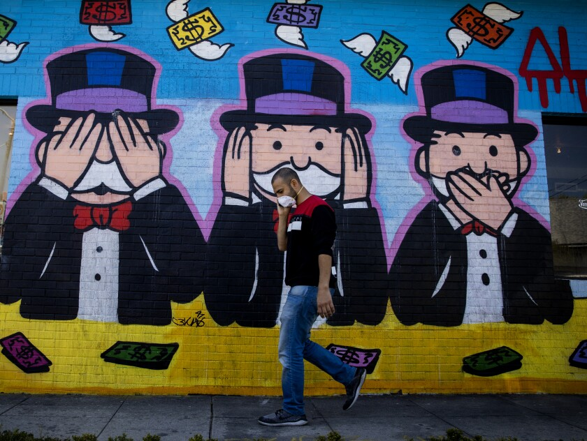 A person in a mask walks in front of a mural