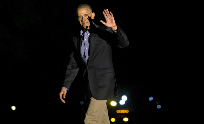 President Barack Obama waves on his return from a shortened visit to Spain, as he walks across the South Lawn of the White House in Washington, Sunday, July 10, 2016. (AP Photo/Jacquelyn Martin)