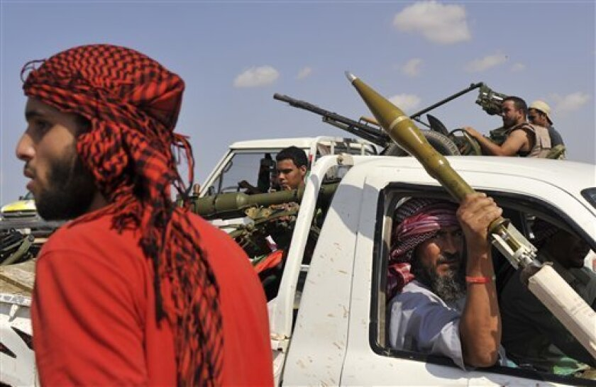 Libyan revolutionary fighters are seen during their attack on the city of Sirte, Libya, Friday, Sept. 30, 2011. Rebel forces are struggling to make headway against loyalist fighters inside the home town of Libya's ousted leader Moammar Gadhafi. (AP Photo/Bela Szandelszky)