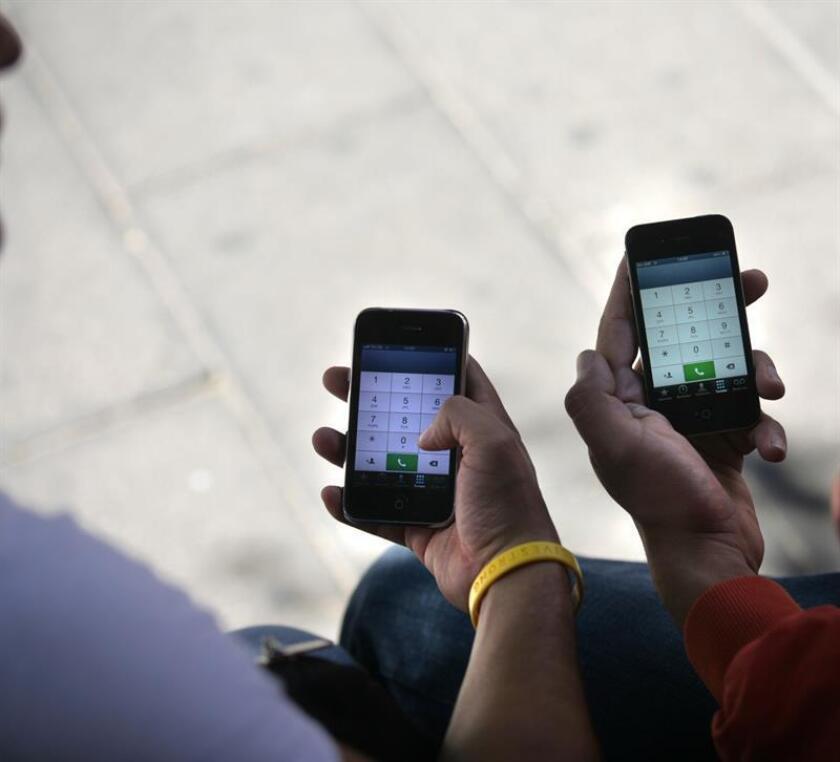 Fotografía de archivo del 23 de enero de 2013 que muestra a dos hombres usando su celular en un parque de Ciudad de México. EFE/Archivo