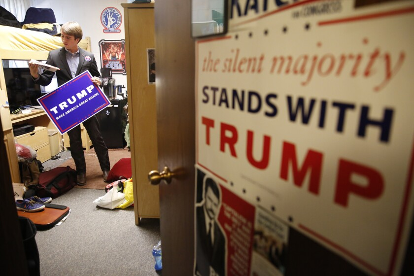 Donald Trump supporter and Westmont College student Jake Lopez grabs a Trump campaign poster in his dorm room to take out on campus in Montecito, Calif.
