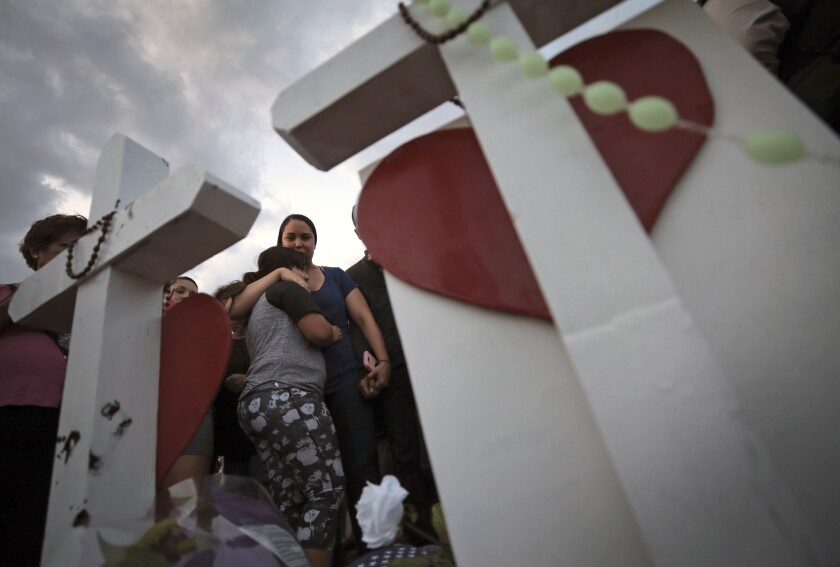 A mother and daughter at a vigil in El Paso
