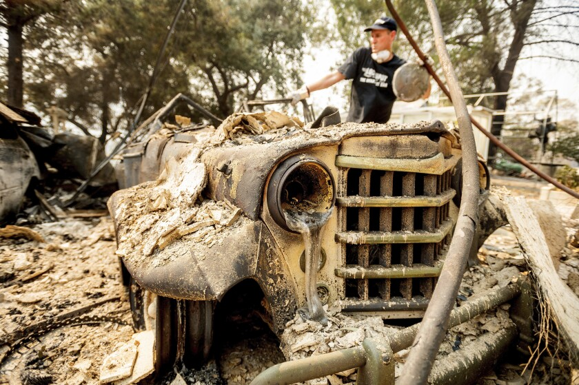 Mark Hanson goes through the remains of a 1951 Willys-Overland Jeepster