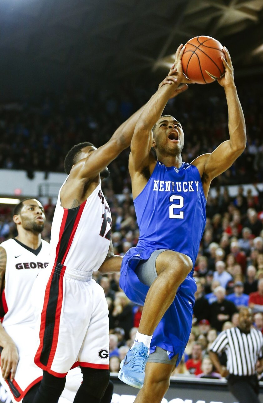 Kentucky guard Aaron Harrison (2) shoots as Georgia guard Kenny Gaines (12) defends in the second half of an NCAA college basketball game Tuesday, March 3, 2015, in Athens, Ga. Kentucky won 72-64 and improved to 30-0. (AP Photo/John Bazemore)