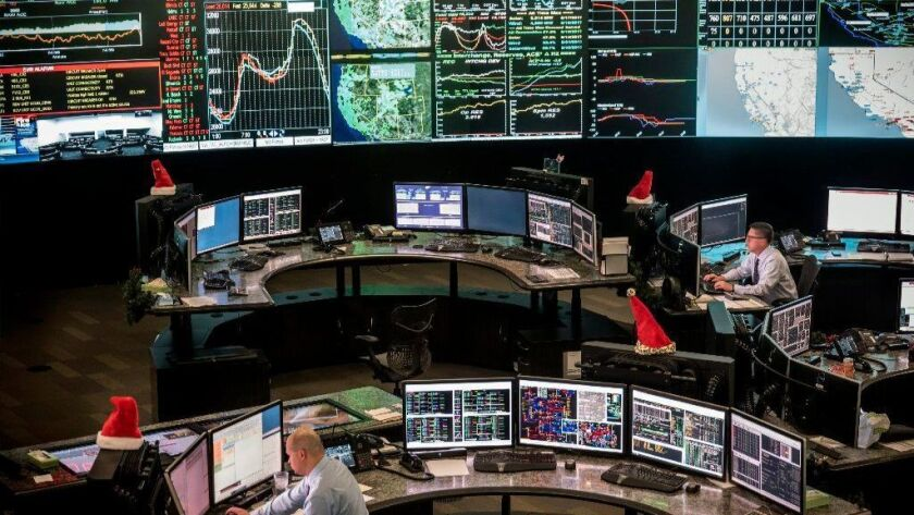 Workers in the CAISO control center monitor energy levels and prices across the California electrical grid. A plan to expand the grid to as many as 14 states is generating praise and criticism.