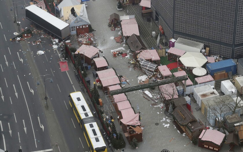 FILE _ In this Dec. 20, 2016 file photo the trailer of a truck stands beside destroyed Christmas market huts in Berlin, Germany. Opposition parties on Friday accused the German government of hampering the work of a parliamentary investigation into the 2016 truck attack on a Christmas market in Berlin. Twelve people were killed and dozens more were injured in the attack carried out by Islamist extremist Anis Amri. (AP Photo/Markus Schreiber, file)
