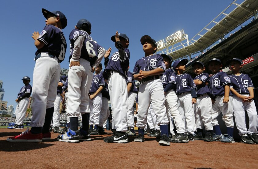 Players from the Lemon Grove Little League take the field in Padres uniforms on opening day for the San Diego Padres Tuesday at Petco Park.
