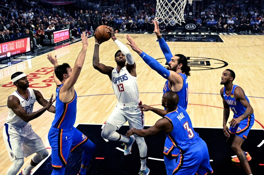 Clippers forward Paul George puts up a shot amid a pack of Thunder defenders during a game Nov. 18 at Staples Center.