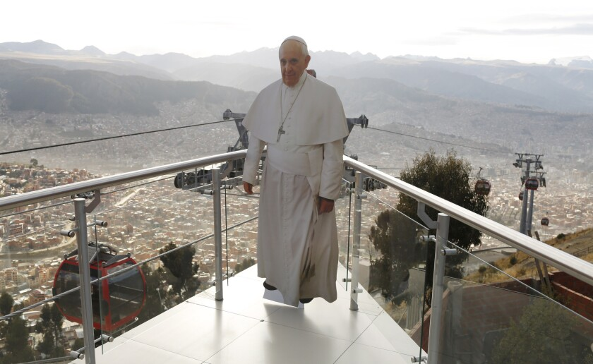 En esta imagen del 3 de julio de 2015, un recortable a tamaño natural con la imagen del papa Francisco colocado sobre La Paz en la plataforma del teleférico en El Alto, donde lo situaron los trabajadores de transportes para que los pasajeros posen en fotografías.