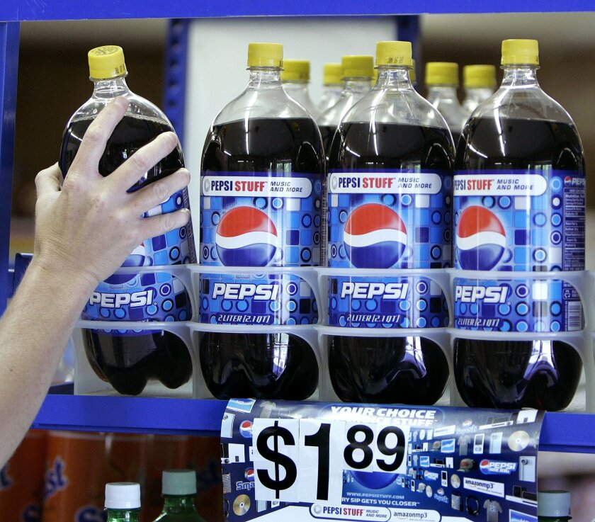 FDILE - In this April 21, 2008 file photo, a customer takes a bottle of Pepsi from a display at T & P Grocery in Hosford, Fla. Big companies of all stripes said their quarters would have been much better if it weren't for the rising dollar. This week, April 23, 2015, the snack and beverage company behind Doritos and Pepsi blamed currency swings for falling revenue during the quarter. It now expects the dollar to knock 11 percentage points off its earnings per share in 2015, up from its previous forecast of 7 percentage points. (AP Photo/Phil Coale)