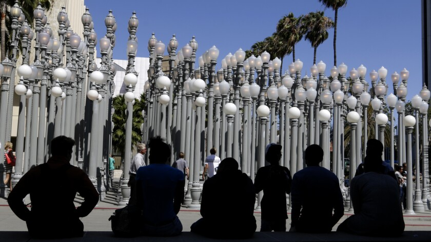 LACMA museum-goers sit in front of the late artist Chris Burden's Urban Light installation in 2015.