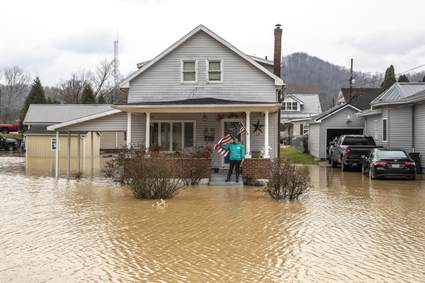 A woman stands on the porch of her home in Paintsville, Ky., as floodwaters approach
