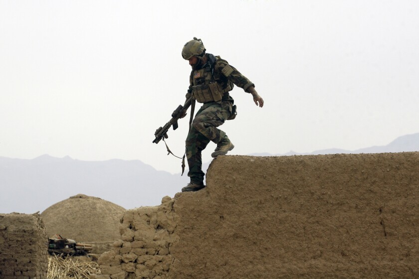 A member of U.S. special operations forces climbs down from a compound wall during a patrol in Afghanistan's Farah province in 2009.