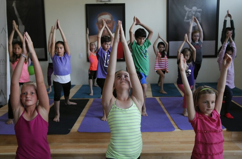 La Costa Heights Elementary School students demonstrate yoga for parents and other adults at the Sonima yoga studio in Encinitas on Wednesday.