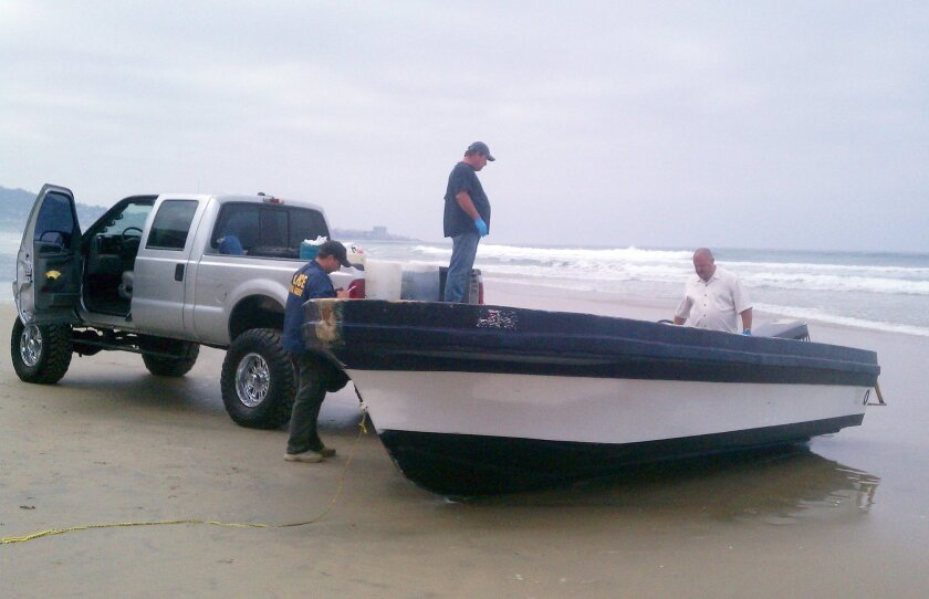Border Patrol and Coast Guard officials investigate an abandoned Panga boat discovered at Black's Beach in March of 2013, similar to the one that came ashore early Friday morning near La Jolla Cove. Greg Wiest