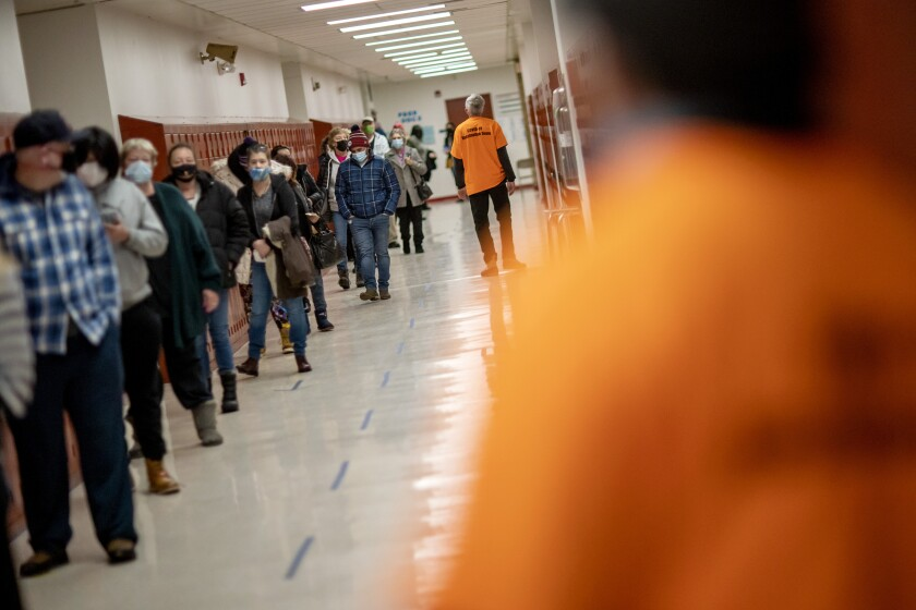 People line up for vaccines at a clinic in Central Falls, R.I.
