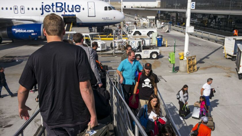 Passengers disembark from a JetBlue Airways plane in Long Beach. The city wants to put an end to underused gate slots.